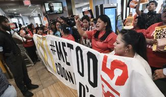 Workers protest inside of a McDonald's restaurant in south Los Angeles on Tuesday, Sept. 18, 2018. Emboldened by the #MeToo movement, McDonald's workers have voted to stage a one-day strike next week at restaurants in 10 cities in hopes of pressuring management to take stronger steps against on-the-job sexual harassment. (AP Photo/Richard Vogel)