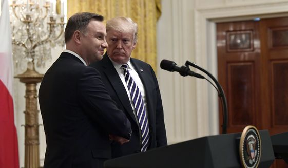 President Donald Trump, right, shakes hands with Polish President Andrzej Duda, left, during a news conference in the East Room of the White House in Washington, Tuesday, Sept. 18, 2018. (AP Photo/Susan Walsh)