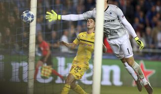 Borussia Dortmund's Christian Pulisic, center, scores his side's first goal as Brugge goalkeeper Karlo Letica dives to stop the ball during a Champions League group A soccer match between Club Brugge and Borussia Dortmund at the Jan Breydel Stadium in Bruges, Belgium, Tuesday, Sept. 18, 2018. (AP Photo/Francisco Seco)