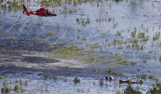 A U.S. Coast Guard helicopter crew prepares to hoist a group of stranded residents from their flooded homes in Burgaw, NC., Tuesday, Sept. 18, 2018. . (AP Photo/Steve Helber)