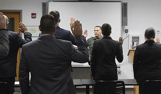 """FILE - In this July 31, 2017, file photo, Yuma Sector Border Patrol Chief Patrol Agent Anthony Porvaznik, center, administers the oath to prospective U.S. Border Patrol agents at the Yuma Sector Border Patrol Headquarters in Yuma, Ariz. A Border Patrol supervisor's arrest in Laredo, Texas on Sunday, Sept. 16, 2018, on allegations that he killed four women has called attention to the problems the agency has had in keeping """"rogue"""" officers off its force as it faces intense pressure to hire thousands more agents. (Randy Hoeft/The Yuma Sun via AP, File)   /The Yuma Sun via AP)"""