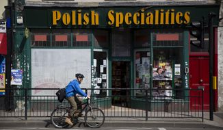 FILE - In this Tuesday, April 5, 2016 file photo, a man cycles past a Polish Specialties shop in London. A British government-commissioned report said Tuesday Sept. 18, 2018, that citizens of European Union countries should not have easier access to the U.K. after Brexit than people from other parts of the world. (AP Photo/Matt Dunham, File)