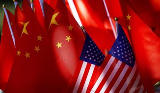 """In this Sept. 16, 2018, photo, American flags are displayed together with Chinese flags on top of a trishaw in Beijing. The American Chamber of Commerce in China says Beijing will """"dig its heels in"""" after U.S. tariff hikes and appealed for a negotiated end to their trade battle. The chamber on Tuesday, Sept. 18 warned a """"downward spiral"""" appears certain after President Donald Trump approved a tariff hike on $200 billion of Chinese imports in a dispute over Beijing's technology policy. (AP Photo/Andy Wong)"""