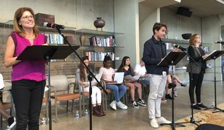"""Actors Vanessa Lock, left, as Betsy DeVos, Cole Sitilides, center, and Jenny Waxman perform in the play """"The Confirmation Hearing for the Secretary of Education"""" in Washington's Arena Stage theater on Monday, Sept. 17, 2018. In the play, about a dozen student actors from local high schools posed as frustrated Democrats and friendly Republicans to grill DeVos on the merits of public education, the role of the federal government in civil rights, and her family wealth. (AP Photo/Maria Danilova)"""
