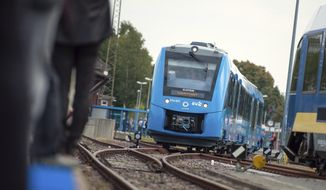 In this Sept. 16, 2018 photo a fuel cell train which is powered by hydrogen arrives in Bremervoerde, northern Germany. It is one of two trains that will go into regular service in 2019. (Philipp Schulze/dpa via AP)