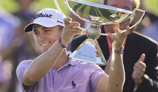 FILE - In this Sept. 24, 2017, file photo, Justin Thomas holds the trophy after winning the Fedex Cup after the Tour Championship golf tournament at East Lake Golf Club in Atlanta. The bonus pool for the PGA Tour season doubles next year to $70 million in a revamped system that pays $15 million to the FedEx Cup champion. (Curtis Compton/Atlanta Journal-Constitution via AP, File)