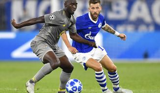 Porto midfielder Danilo, left, and Schalke forward Guido Burgstaller challenge for the ball during the Champions League group D soccer match between FC Schalke 04 and FC Porto at the Arena AufSchalke in Gelsenkirchen, Germany, Tuesday, Sept. 18, 2018. (AP Photo/Martin Meissner)
