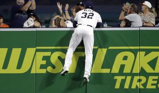 San Diego Padres center fielder Franmil Reyes (32) watches from the wall as a fan tries to catch a home run ball hit by the San Francisco Giants' Brandon Crawford during the fourth inning of a baseball game Monday, Sept. 17, 2018, in San Diego. (AP Photo/Gregory Bull)