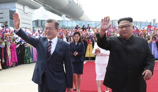 South Korean President Moon Jae-in and North Korean leader Kim Jong-un, right, wave during a welcoming ceremony at Sunan International Airport in Pyongyang in North Korea, Tuesday, Sept. 18, 2018. (Pyongyang Press Corps Pool via AP)