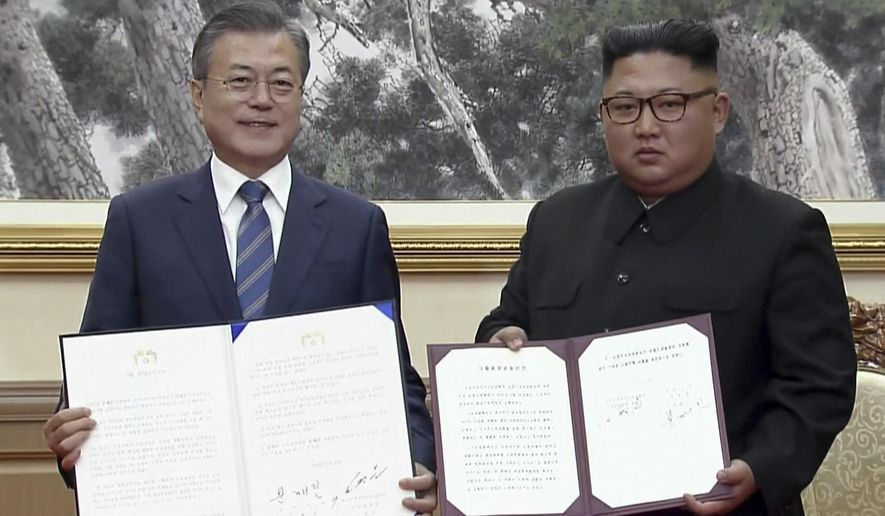 In this image made from video provided by Korea Broadcasting System (KBS),  South Korean President Moon Jae-in, left, and North Korean leader Kim Jong Un pose after signing documents in Pyongyang, North Korea Wednesday, Sept. 19, 2018.(Korea Broadcasting System via AP)