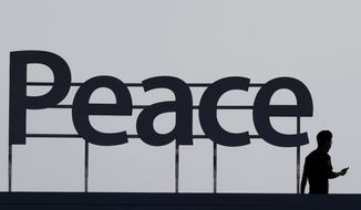 """FILE - In this Aug. 15, 2018, file photo, a man walks by a """"Peace"""" sign before a ceremony to celebrate Korean Liberation Day in Seoul, South Korea. At the heart of the current impasse in nuclear diplomacy with North Korea is a seemingly straightforward demand by both North and South Korea for an end to the Korean War. (AP Photo/Lee Jin-man, File)"""