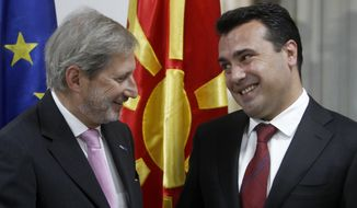 "European Union's enlargement commissioner Johannes Hahn, left, talks with Macedonian Prime Minister Zoran Zaev, during their meeting in Skopje, Macedonia, Tuesday, Sept. 18, 2018.  Hahn has urged Macedonians to back a name deal referendum planned for the end of this month that will change the country name to ""North Macedonia"" and pave the way for accession to EU and NATO.(AP Photo/Boris Grdanoski)"