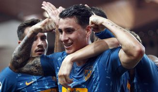 Atletico defender Jose Maria Gimenez, center, celebrates his goal with teammates during the Champions League Group A soccer match between Monaco and Atletico Madrid at the Louis II stadium in Monaco, Tuesday, Sept. 18, 2018. (AP Photo/Claude Paris)