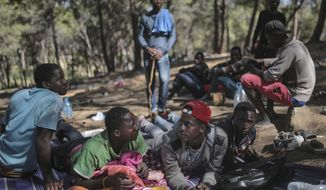 In this Wednesday, Sept. 5, 2018 photo, sub-Saharan migrants aiming to cross to Europe take shelter in a forest overlooking the neighborhood of Masnana, on the outskirts of Tangier, Morocco. Hundreds of sub-Saharan migrants escaping poverty and violence in their home countries are fleeing to forests to escape police raids in the northern Moroccan port city of Tangiers _ only to be chased from their makeshift camps. (AP Photo/Mosa'ab Elshamy)