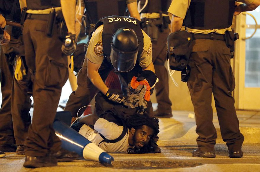 In this Sept. 17, 2017, file photo, police arrest a man as demonstrators march in response to a not guilty verdict in the trial of former St. Louis police officer Jason Stockley in St. Louis. Stockley was acquitted in the 2011 killing of a black man following a high-speed chase. More than a dozen people arrested in the 2017 protest in St. Louis are suing the city, police officers and their supervisors, alleging they were roughed up, pepper sprayed and illegally detained. Federal lawsuits were filed Monday, Sept. 17, 2018, a year to the day after the downtown protest.  (AP Photo/Jeff Roberson) **FILE**