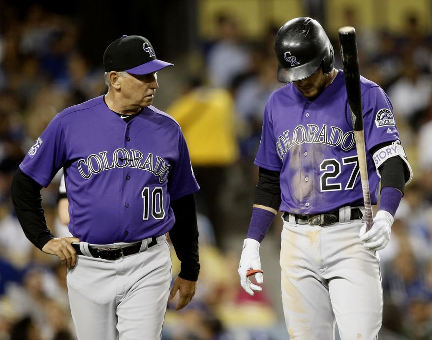 An injury forces Colorado Rockies' Trevor Story (27) to walk off the field with manager Bud Black (10) during an at-bat in the fourth inning of a baseball game against the Los Angeles Dodgers in Los Angeles, Monday, Sept. 17, 2018. (AP Photo/Alex Gallardo)