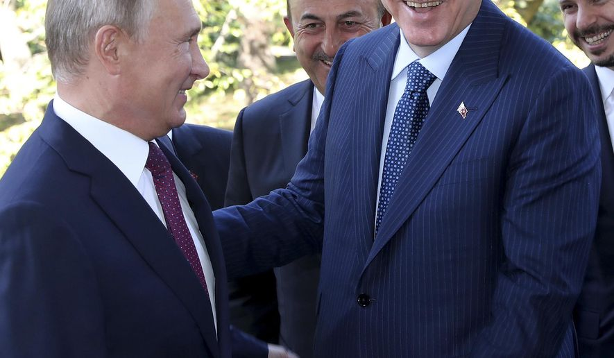 Russian President Vladimir Putin, left, welcomes Turkey's President Recep Tayyip Erdogan, prior to their talks at the Bocharovy Ruchei residence, in Sochi, Russia, Monday, Sept. 17, 2018. The leaders of Russia and Turkey agreed Monday to establish a demilitarized zone in Syria's Idlib region. (Presidential Press Service via AP, Pool)
