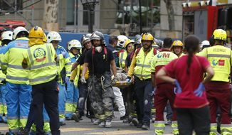 An injured worker is carried on a stretcher after scaffolding collapsed at the Ritz hotel undergoing renovation in Madrid, Spain, Tuesday, Sept. 18, 2018. One construction worker was killed and at least 11 injured after wrought iron work on the sixth floor of the hotel collapsed dragging down five floors of internal scaffolding and the workers at the site. (AP Photo/Paul White)