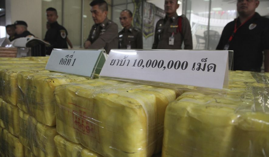 Thai policemen stand in front of seized methamphetamine pills at the Narcotics Suppression Bureau during a press conference in Bangkok, Thailand, Tuesday, Sept. 18, 2018. Thai police said it has made three drug-related arrests in less than a week, seizing 10 million methamphetamine pills hidden in chicken manure in the largest case. (AP Photo)
