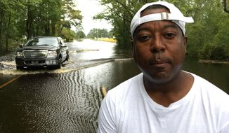 Famous Roberts poses for a portrait as an SUV plows through floodwaters on NC 41 outside Trenton, N.C., on Monday, Sept. 17, 2018. Roberts chose to ride out Hurricane Florence in Trenton, partly because the forecast strength had dropped from a Category 4 to a Category 1. (AP Photo/Allen G. Breed)