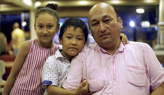 In this Aug. 25, 2018, photo, Omir Bekali, right, an outspoken critic of China's internment camps for Muslims, poses for a picture with his children Aisha, left, and Ibrahim in a cafe in Istanbul. Bekali who now lives in Istanbul said Tuesday, Sept. 18, 2018, that his wife and son face potential deportation to China because Turkish authorities might bar them from entering the country. (AP Photo/Dake Kang)