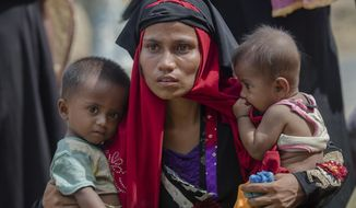 FILE - In this Sunday, Oct. 22, 2017, file photo, a Rohingya Muslim woman, Rukaya Begum, who crossed over from Myanmar into Bangladesh, holds her son Mahbubur Rehman, left and her daughter Rehana Bibi, after the government moved them to newly allocated refugee camp areas, near Kutupalong, Bangladesh. A team of independent investigators examining alleged violence and killings in Myanmar that caused hundreds of thousands of Rohingya Muslims to flee their homes have issued a searing critique of the United Nations' own operations in the country just as bloodshed erupted in August 2017. (AP Photo/Dar Yasin, File)