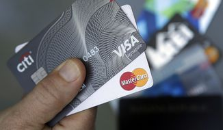FILE- In this June 15, 2017, file photo, credit cards are displayed in Haverhill, Mass. Visa and Mastercard say they and several banks will pay $6.2 billion to settle part of a long-running lawsuit brought by merchants over fees on credit card transactions. (AP Photo/Elise Amendola, File)