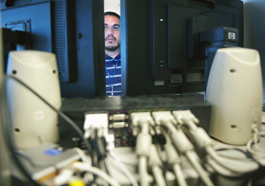 Computer forensic examiner Gil Moreno works on several hard drives association with a crime, at the Department of Defense Cyber Crime Center in Linthicum, Thursday, Aug. 11, 2011. Hackers and hostile nations are launching increasingly sophisticated cyberattacks against U.S. defense contractors. And the Pentagon is extending a program to help protect its prime suppliers, while serving as a possible model for other government agencies. Pentagon analysts are investigating a growing number of cases involving the mishandling or removal of classified data from military and corporate systems. Defense officials say intrusions into defense networks are now close to 30 percent of the Pentagon's Cyber Crime Center's workload. (AP Photo/Cliff Owen) **FILE**