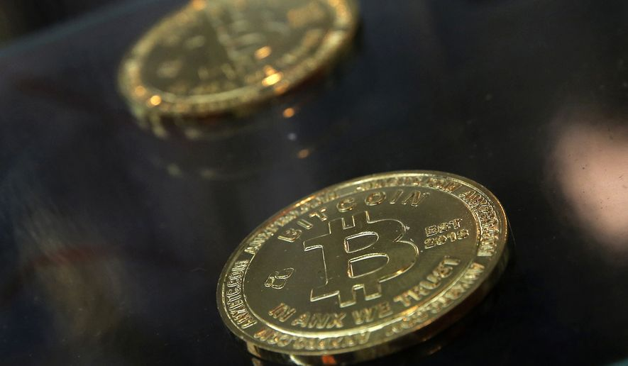 In this Dec. 8, 2017, photo, coins are displayed next to a Bitcoin ATM in Hong Kong. (AP Photo/Kin Cheung) **FILE**