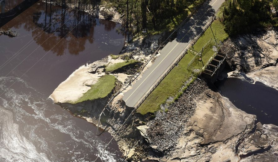 The dam and roadway at Alton Lennon Drive in Boiling Spring Lakes, N.C. is washed away Wednesday Sept. 19, 2018 after water from Hurricane Florence overran it earlier this week. (Ken Blevins/The Star-News via AP)