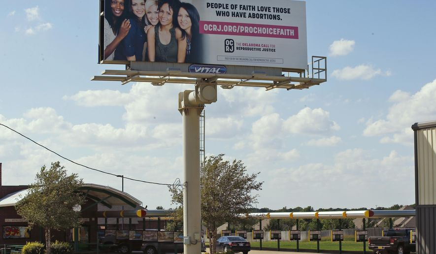 In this Sept. 18, 2018 photo, a billboard stands in Edmond, Okla. The billboards are part of a campaign from Oklahoma Call for Reproductive Justice in partnership with Oklahoma faith leaders to spread awareness that people of faith support those who have abortions. (AP Photo/Sue Ogrocki)