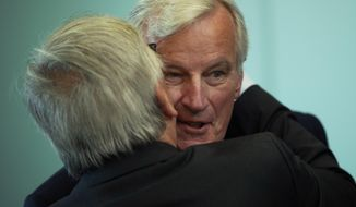 EU chief Brexit negotiator Michel Barnier, background, is kissed by European Commission President Jean-Claude Juncker before a meeting at the European Commission headquarters in Brussels, Wednesday, Sept. 19, 2018. British Prime Minister Theresa May urged EU leaders to compromise and back her Brexit blueprint Wednesday, ahead of a key meeting of the bloc's leaders in Salzburg, Austria. (AP Photo/Francisco Seco)