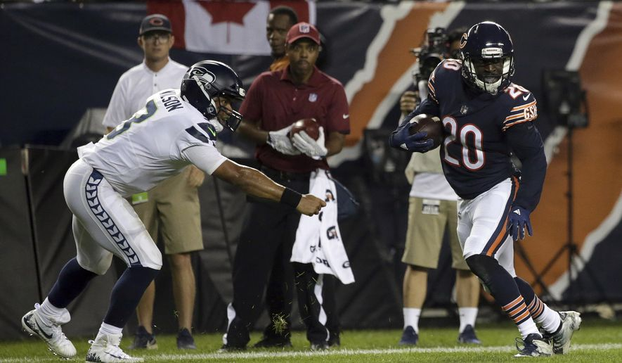 Chicago Bears defensive back Prince Amukamara (20) runs away from Seattle Seahawks quarterback Russell Wilson (3) to the end zone for a touchdown after intercepting a pass during the second half of an NFL football game Monday, Sept. 17, 2018, in Chicago. (AP Photo/David Banks)