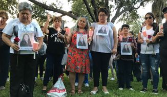 Dozens of family members and friends of four women who authorities say were killed by a U.S. Border Patrol agent gather for a candlelight vigil at a park in downtown Laredo, Texas, on Tuesday, Sept. 18, 2018. Juan David Ortiz was arrested Saturday while hiding in a hotel parking garage. Investigators believe he fatally shot the four victims during separate attacks after taking each of them to desolate areas outside of Laredo. Investigators say a fifth victim escaped and contacted authorities. (AP Photo/Susan Montoya Bryan)