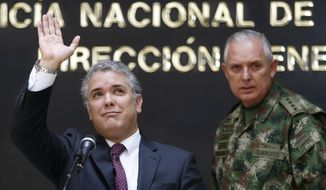 "Colombia's President Ivan Duque, left, waves next to the Commander of the Armed Forces Gen. Alberto Mejia, during a press conference at police headquarters in Bogota, Colombia, Wednesday, Sept. 19, 2018. Duque said that Colombian armed forces continue with operations against a dissident rebel of the now disbanded Revolutionary Armed Forces of Colombia known as ""Guacho"". (AP Photo/Fernando Vergara)"