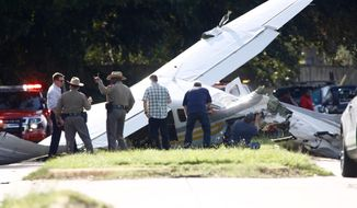 Investigators look at a small plane that crashed just west of Highway 6, Wednesday, Sept. 19, 2018, in Sugar Land, Texas. Authorities say a small plane operated by the Drug Enforcement Administration crashed on the street in suburban Houston, hitting two vehicles and injuring one person. (Mark Mulligan/Houston Chronicle via AP)
