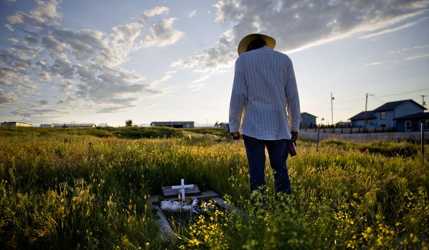 In this July 14, 2018, file photo, Kenny Still Smoking stands over the tombstone of his 7-year-old daughter, Monica, who disappeared from school in 1979 and found frozen on a mountain, as he visits her grave on the Blackfeet Indian Reservation in Browning, Mont. A top U.S. Justice Department official says it's doubling the amount of federal funding for tribal public safety and crime victims as it seeks to tackle the high-rates of violence against Native American women. The announcement on Wednesday, Sept. 19, 2018, comes amid increased focus on the deaths and disappearances of Native American women and girls in the United States. (AP Photo/David Goldman, File)