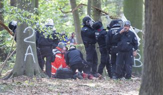 A man receives medical treatment after he fell off a tree at the Hambach forest in Kerpen, Germany, Wednesday, Sept. 19, 2018. Activists are protesting against the expansion of a coal strip mine in western Germany that would entail the chopping down of an ancient forest. (Christophe Gateau/dpa via AP)