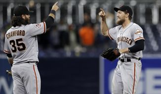 San Francisco Giants right fielder Hunter Pence, right, and shortstop Brandon Crawford (35) celebrate after the Giants defeated the San Diego Padres 5-4 in a baseball game Tuesday, Sept. 18, 2018, in San Diego. (AP Photo/Gregory Bull)