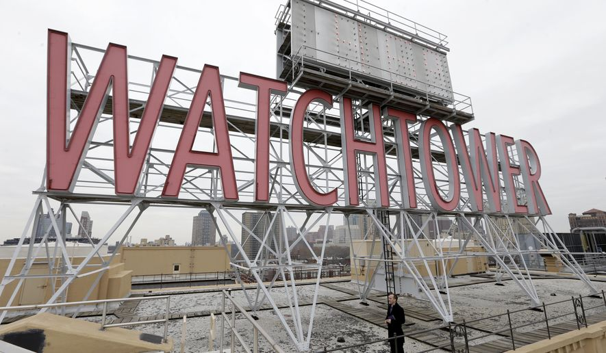 In this Wednesday, Dec. 9, 2015, file photo, the iconic Watchtower sign is seen on the roof of 25-30 Columbia Heights, then world headquarters of the Jehovah's Witnesses, in the Brooklyn borough of New York.  (AP Photo/Seth Wenig)
