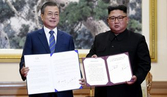 South Korean President Moon Jae-in, left, and North Korean leader Kim Jong Un hold documents after signing at the Paekhwawon State Guesthouse in Pyongyang, North Korea, Wednesday, Sept. 19, 2018. This week's inter-Korean summit talks ended with a set of sweeping agreements on denuclearization of the Korean Peninsula, reducing a military standoff and other reconciliation issues. (Pyongyang Press Corps Pool via AP)