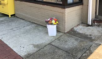 Residents in the Logan Circle neighborhood placed a clutch flowers where a female jogger was fatally stabbed Tuesday night in the 1400 block of 11th Street NW. Police are offering a $25,000 reward for information that leads to the arrest of the man who stabbed Wendy K. Martinez, 35. (Photo by Jeff Mordock / The Washington Times)