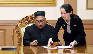 Kim Yo Jong, right, sister of North Korean leader Kim Jong-un, helps Kim sign joint statement following the summit with South Korean President Moon Jae-in at the Paekhwawon State Guesthouse in Pyongyang, North Korea, Wednesday, Sept. 19, 2018. (Pyongyang Press Corps Pool via AP)