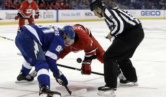 """Linesman Libor Suchanek (60) drops the puck for Tampa Bay Lightning center Steven Stamkos (91) and Carolina Hurricanes left wing Jordan Martinook (48) during the first period of an NHL preseason hockey game Tuesday, Sept. 18, 2018, in Tampa, Fla. If players need camp to prepare for the start of the season, the officials are no different. """"We get to refresh the rules, and it gets us back in the flow,"""" veteran linesman Tony Sericolo said. """"You start thinking hockey again because for a couple of months, we're home, we're relaxing."""" (AP Photo/Chris O'Meara)"""