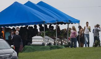FILE – In this May 3, 2016, file photo, mourners gather around caskets for six of the eight members of the Rhoden family found shot April 22, 2016, at four properties near Piketon, Ohio, during funeral services at Scioto Burial Park in McDermott, Ohio.  The Ohio Supreme Court has sided with a newspaper seeking to view autopsy reports and photos in the still-unsolved slayings of the eight Rhoden family members. The court ruled unanimously Wednesday, Sept. 19, 2018, in favor of the Cincinnati Enquirer, saying Ohio law allows reporters to view preliminary autopsy and investigative notes and findings, and photographs.  (AP Photo/John Minchillo, File)