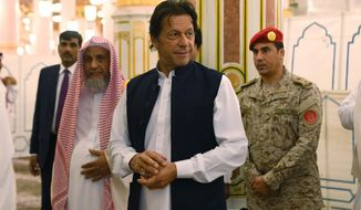In this Tuesday, Sept. 18, 2018, photo released by the state-run Saudi Press Agency, Pakistani Prime Minister Imran Khan, center, visits the Prophet's Mosque in Medina, Saudi Arabia. Khan, a former cricketer, is on a tour of Saudi Arabia and the United Arab Emirates as part of his first overseas trip since taking office. (Saudi Press Agency via AP)