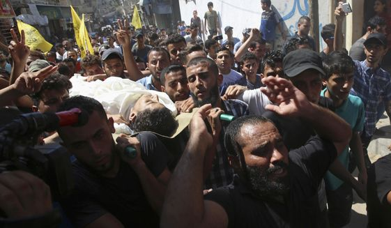 Mourners chant Islamic slogans while carrying the body of Ahamd Omar, 20, during his funeral in the Shati refugee camp, Wednesday, Sept. 19, 2018. Omar was killed Tuesday during a protest at the entrance of Erez border crossing between Gaza and Israel. (AP Photo/Adel Hana)