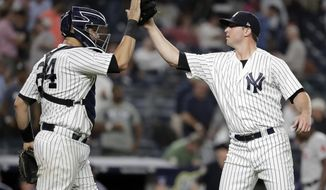 New York Yankees relief pitcher Zach Britton, right, celebrates with catcher Gary Sanchez after the Yankees defeated the Boston Red Sox 3-2 during a baseball game Tuesday, Sept. 18, 2018, in New York. (AP Photo/Julio Cortez)