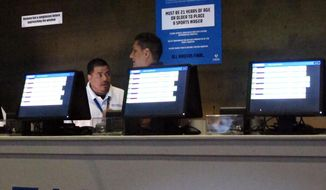 This July 14, 2018 photo, workers at the FanDuel sports book at the Meadowlands Racetrack in East Rutherford N.J. prepare to take bets moments before opening.   New Jersey gambling regulators are investigating whether FanDuel should be ordered to pay a New Jersey man $82,000 for a bet he made on a football game at what the company said were erroneously high odds. (AP Photo/Wayne Parry)