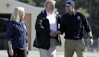 President Donald Trump shakes hands with FEMA Administrator Brock Long as Homeland Security Secretary Kirstjen Nielsen watches after visiting areas in North Carolina and South Carolina impacted by Hurricane Florence, Wednesday, Sept. 19, 2018, at Myrtle Beach International Airport in Myrtle Beach, S.C. (AP Photo/Evan Vucci)